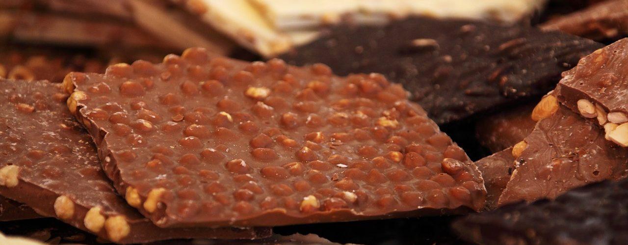 Photo de 3 types de chocolat noir blanc et au lait, ils sont incrustés de noisettes