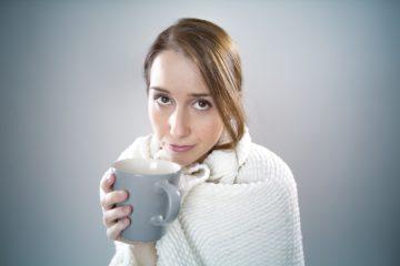 Photo d'une femme qui a froid et se couvre les épaules avec un plaid et une tisane