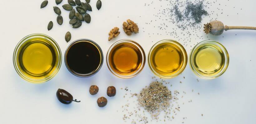 Photo d'huiles vegetales à coter de leurs fruits correspondants