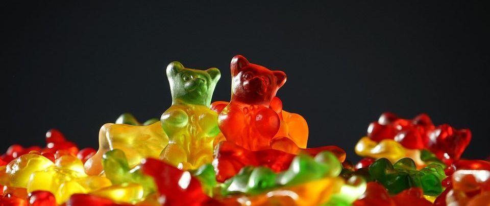 Photo de bonbon en forme de petit ours de toute les couleurs sur un fond noir