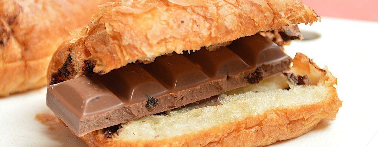 Photo d'une chocolatine coupée en deux et fourrée de 5 carreaux de chocolat au lait