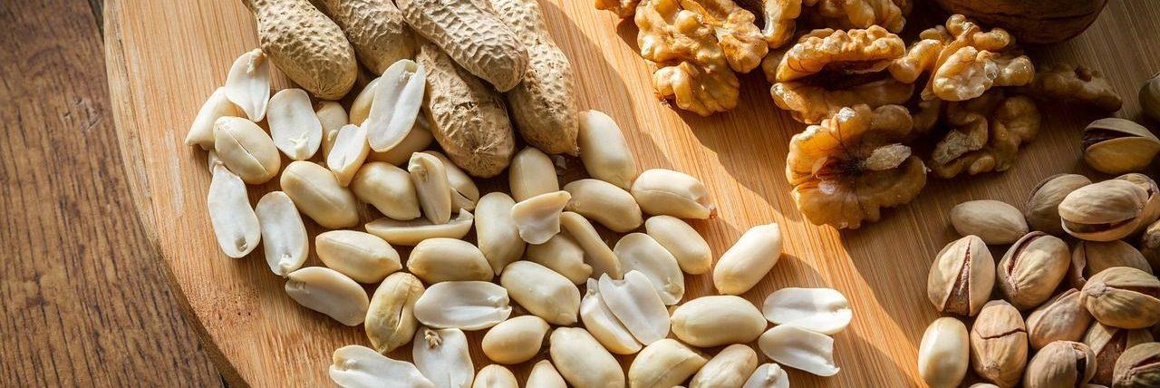 Photo d'oléagineuses posé sur un plateau en bois, on peut y voir des noix, des cacahuètes et noix de cajous