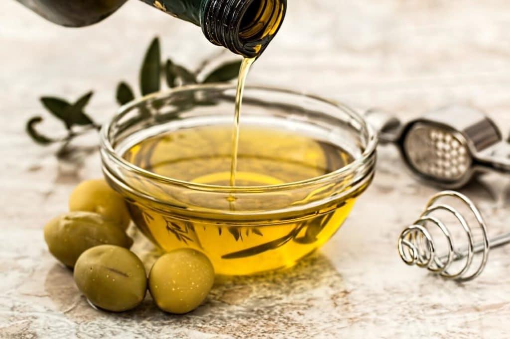 Photo d'huile d'olive avec quelques olives à coter