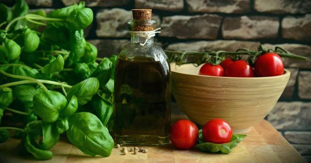 Photo dune bouteille dhuile dolive, à gauche du basilic, à droite des tomates