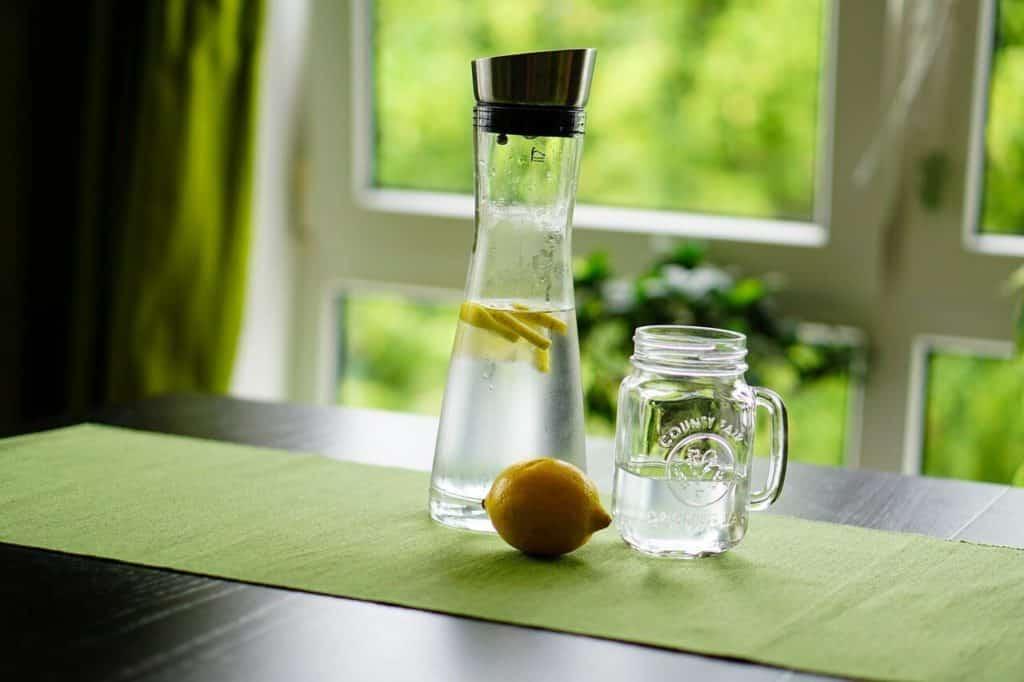 Photo du carafe d'eau posé sur une table, un citron infuse dans celle-ci tandis qu'un autre est posé à coter