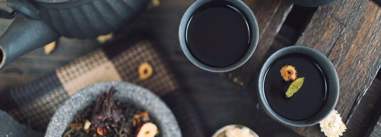 Photo de tasses de thé rempli avec a coté du thé séché près à être infusé. Il y a aussi une théière à gauche