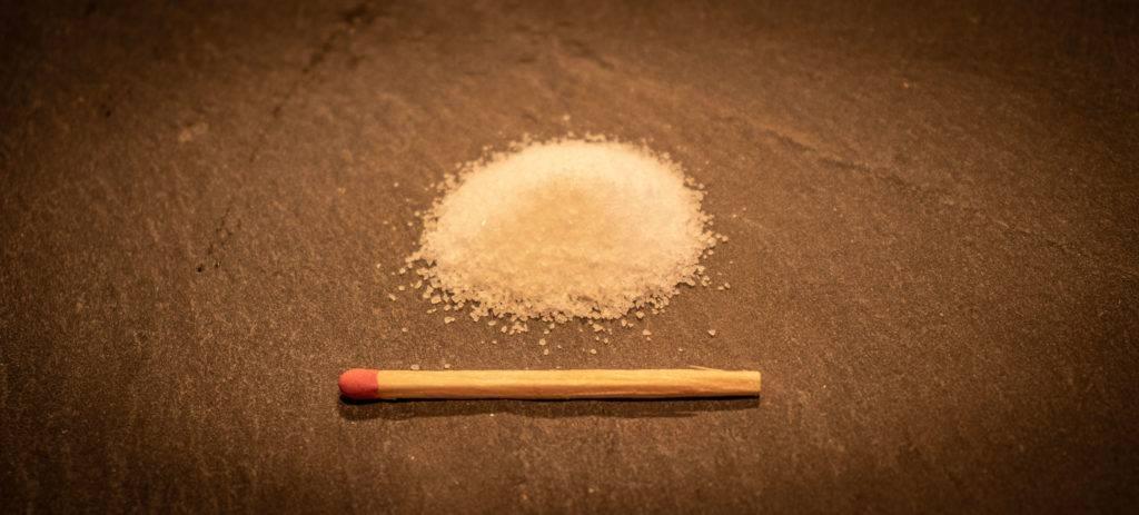 Photo de Thomas Hartmann naturopathe et hypnothérapeute représentant 2.4g de sodium pur à coter d'une allumette pour se représenter la dose à respecter pas jour.