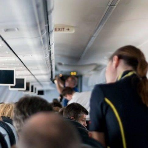 Photo dans un avion de ligne, on y voit des hôtesses et passagers embarquer.