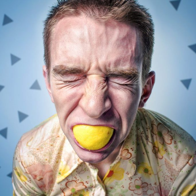 photo d'un homme qui croque un citron d'énervement