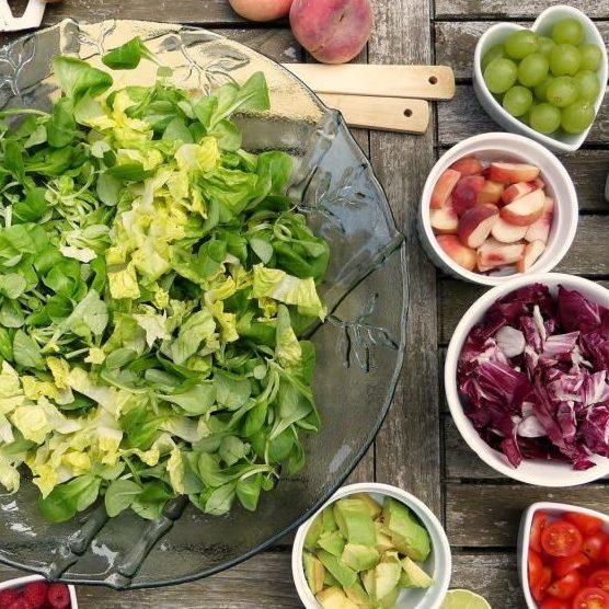 photo d'une table avec de la nourriture placé dans des bols. Ils sont remplis de salades, fruits et légumes frais.