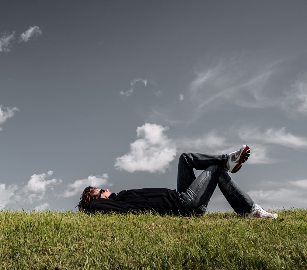 Photo d'un homme allongé dans l'herbe entrain de se reposer