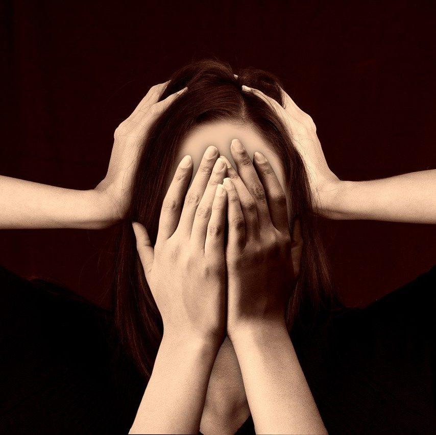 La photo représente une femme se mettant les mains sur le visage. on peut constater qu'elle est en souffrance.