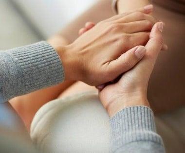 Photo d'une personne tenant les main d'une autre personne pour l'accompagner dans ses troubles de santé