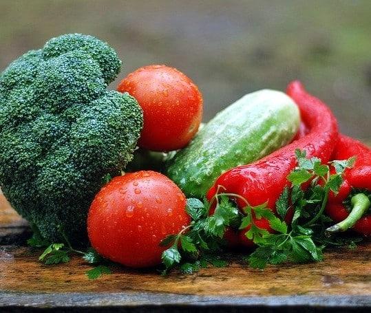 Photo de légumes frais, on retrouve des tomates, brocolis, un concombre et des piments.