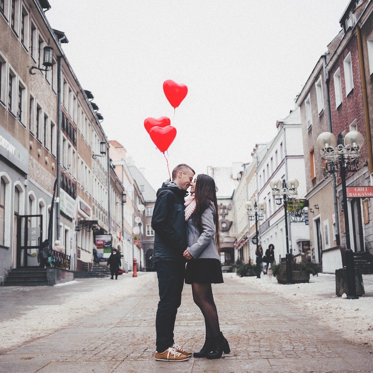 Photo d'un jeune couple qui s'embrasse au milieu d'une rue. Ils tiennent en main des ballons en forme de cœurs