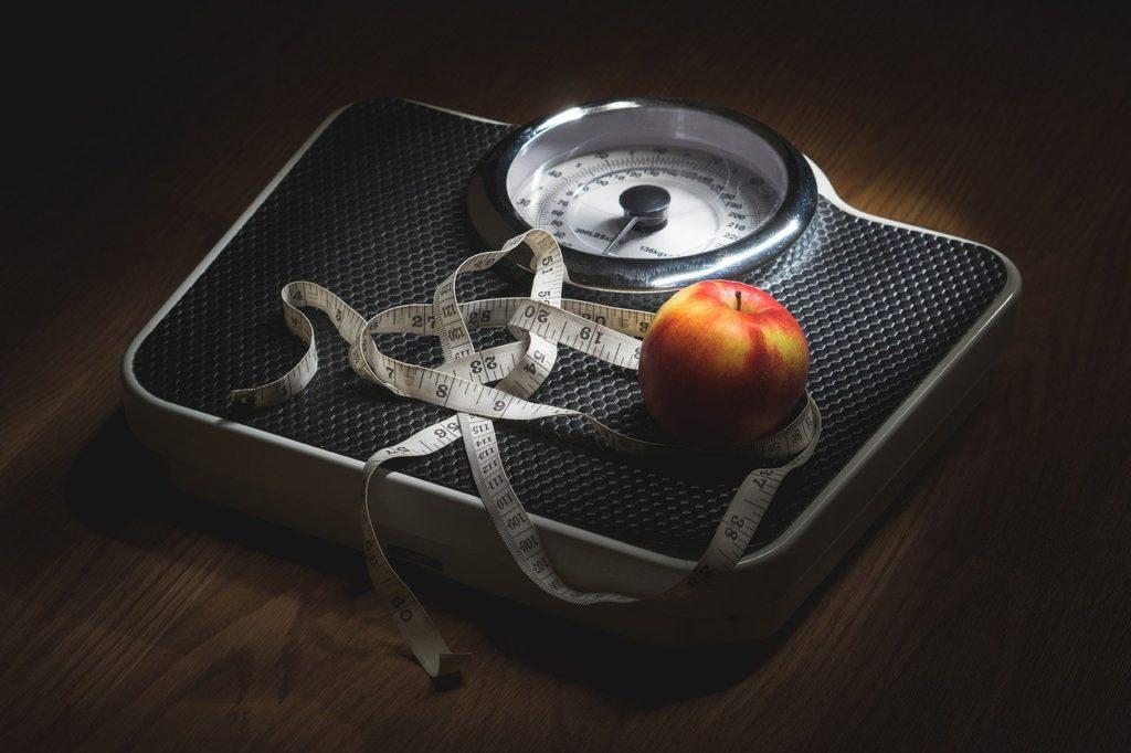 Photo d'une balance ou est posé une pomme, un mètre pour faire référence à aux bonnes résolutions de perdre du poids au soir du Nouvel An
