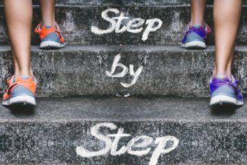 Photo de deux personnes ayant pris la bonne résolution de faire du sport, il y a écrit step by step, étape par en étape en français au milieu de la photo.