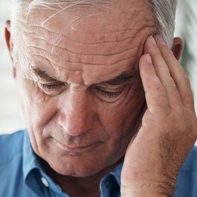 Photo d'une personne se tenant la tête, on peut penser qu'elle a mal à la tête.