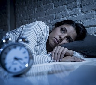 Photo d'une personne cherchant le sommeil en regardant son réveil
